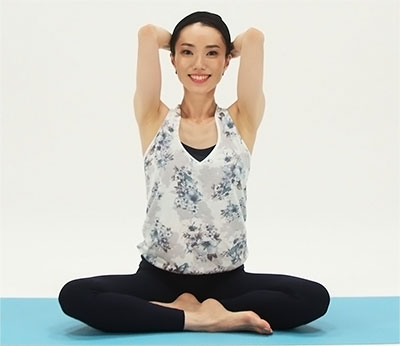 あぐらの姿勢で、背骨の一番下の仙骨と頭のラインを真っ直ぐにして、頭の後ろで手を組み、ひじを緩めます