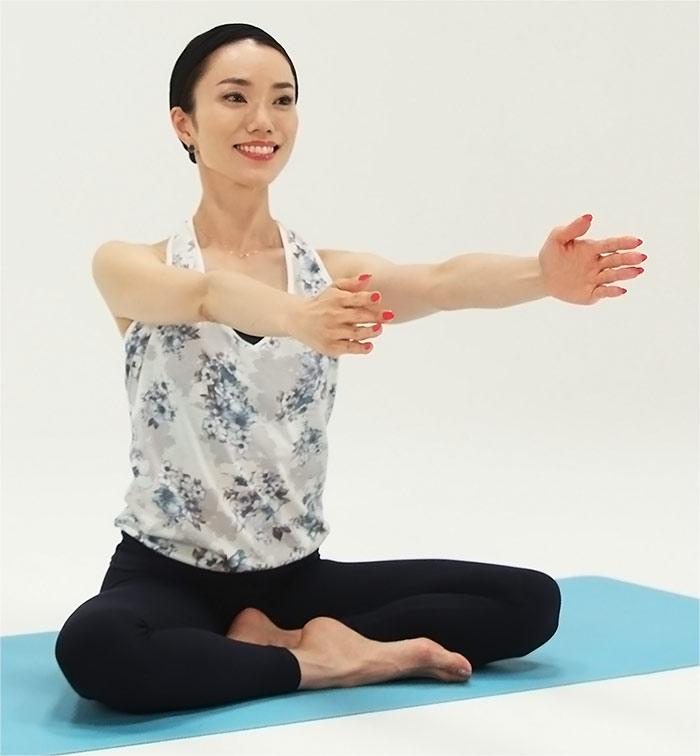 あぐらになり、両手を前に伸ばし、肩幅に開きます。そこから片方の手をゆっくり前に持っていきます。