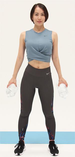 両手にペットボトルを持ち、足を肩幅程度に開いて立ちます。