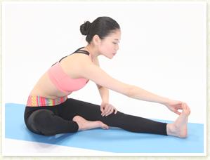 伸ばした足先の外側を右手で掴み左手で押さえます。
