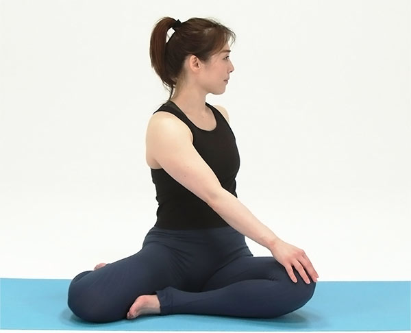 長座になり背骨を長く伸ばして、手は胸の前で組み、左のかかとを手前に引き寄せ、ひざは外側に