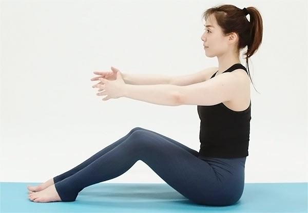 ひざを立てて座り、首はすくめず背骨を長く伸ばします。手で大きなボールを抱えるように、両手を前に