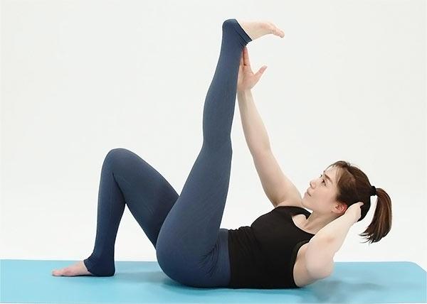 左足をまっすぐ上に伸ばし、足首は90度に。 右手を内ももに添え、息を吐きながら上体を起こす