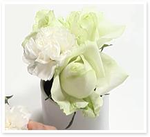 サブ花材1のカーネーションを間に挿していきます。トップの茎の長さは、器の高さ+3㎝を目安にカットします。バラが引き立つように低めに挿します。
