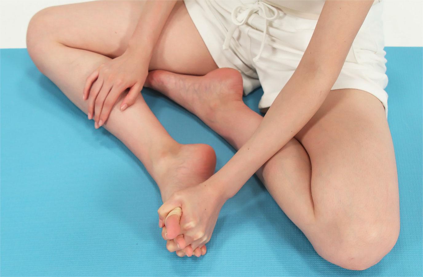 足の指と手の指を絡ませます。手をギューッと握ったら緩めます