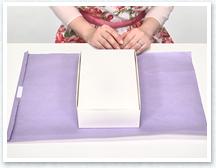 紙を裏返して右端を折り、中央に両面テープを貼ったら、箱を裏側に向けて中央に置きます。