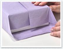 合わせ目のある上側の紙を箱に沿って下に折り、横は三角に折ります。