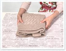 畳んだセーターの表を下にして紙の中心に置きます。