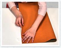 両面テープのはくり紙を少しめくって外側に折り紙を半分に折って角を貼り合わせ