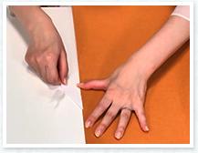 角から左手で押さえた部分のはくり紙を右手ではがしながら貼り合わせ左手を少しずつ下にずらしながら貼る