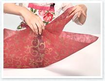 ボトルを不織布の中央に置き、前後の紙を立ち上げ、間の紙を内側に入れ前後に羽根を作ります。