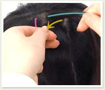 右の毛束を真ん中の毛束の下側に重ねる。
