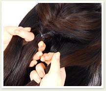 両サイドの髪を取り、結んだ髪と合わせて3つの毛束を作る。