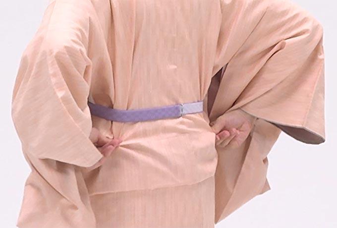 背中のシワを伸ばします。背中の縫い目を引き、縦シワは脇に寄せます。