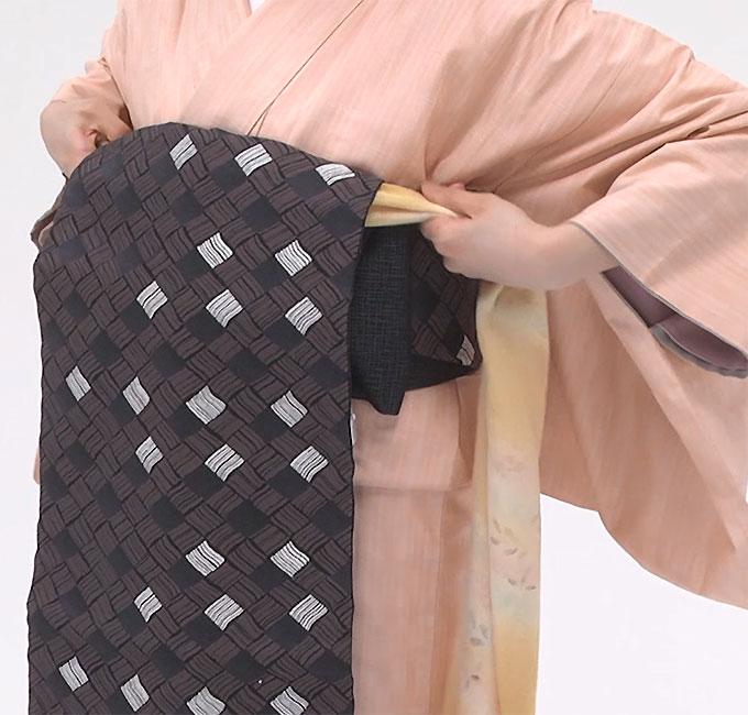 タレの裏側に、先ほどつくっておいた帯枕を当てて持ち上げ、帯の上のラインに重ねます。