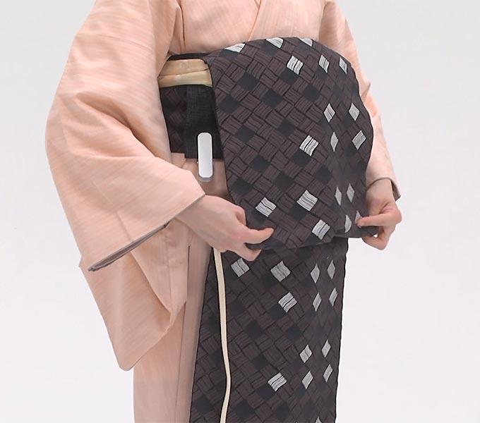 次に、タレの足の付け根くらいの位置に帯締めを当てて、帯をつかみます。