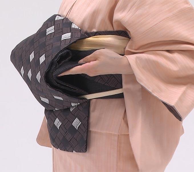胴帯に固定していた手先のクリップを外し、手先を持ち上げて、帯のふくらみをつくります。