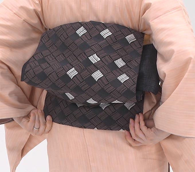 帯板が前中心に来たら、今度は帯だけを後ろに回します。帯が背中に回ったら、タレを下ろします。