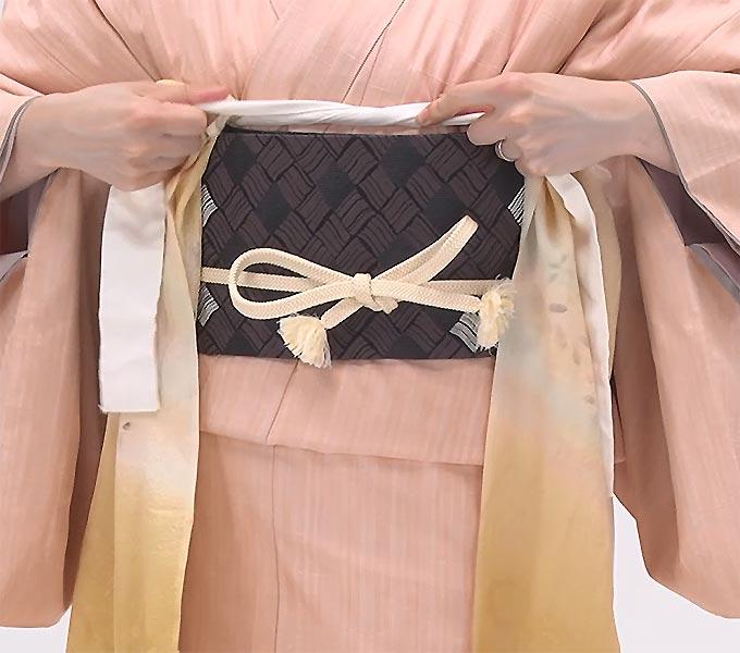 次に、帯揚げを慎重に解き、中の腰紐を帯結びが背中につくようにしっかり結び直します。蝶々結びをして帯の中にしまいます。