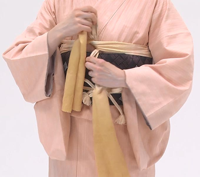 帯揚げは、端を内側に折り、脇からきれいに整えて、左を上に重ねてひと結びし、立てます。