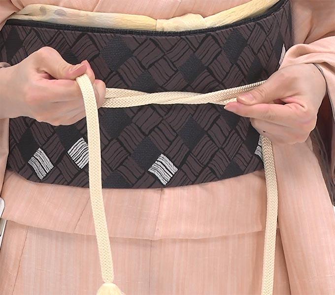 次に、帯締めを結び直します。左手の帯締めを上に重ねてひと結びし、しっかり締めます。