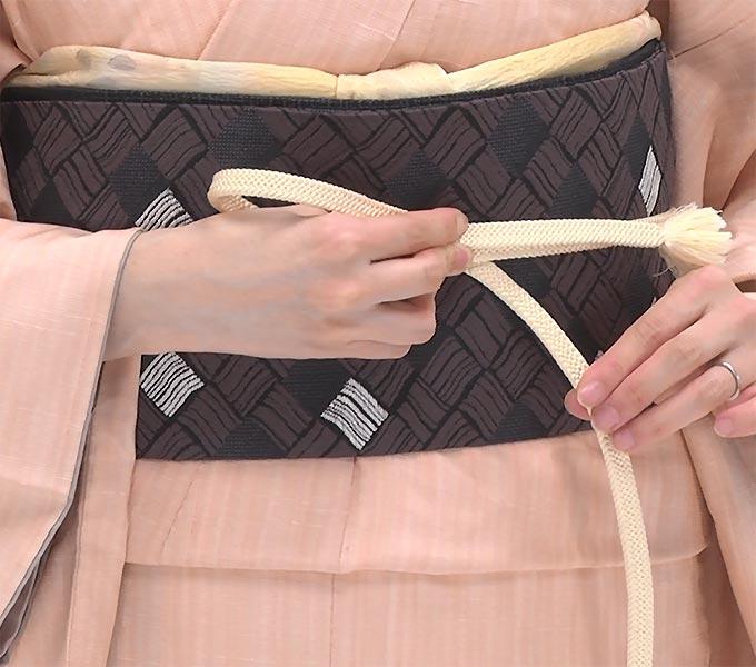 上の帯締めで輪をつくり、もう片方の帯締めの上で緩まないように押さえます。