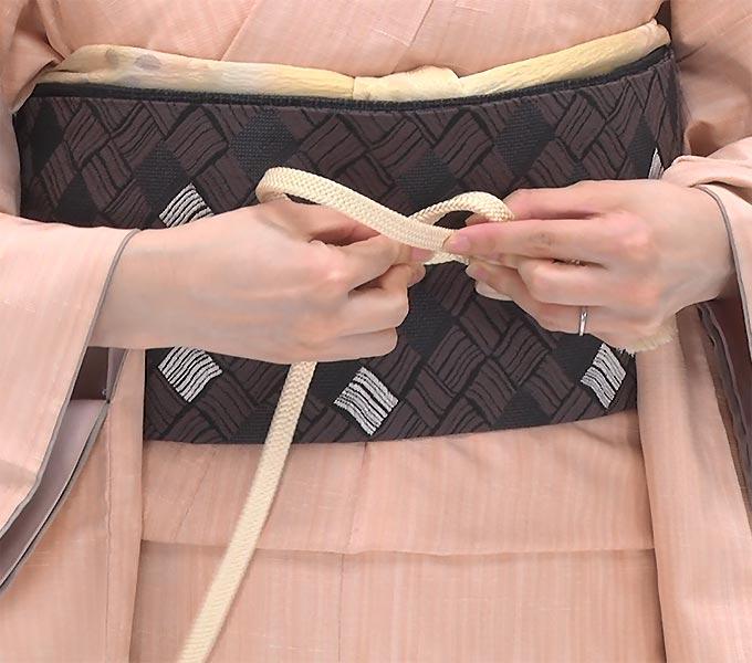 下の帯締めを真上に持ち上げ、そのまま輪に通します。