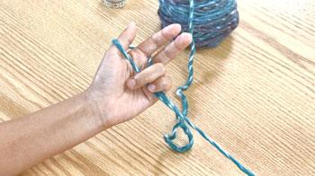垂れている2本の糸を薬指と小指で軽く握ります