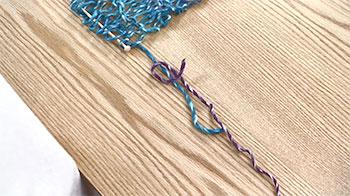 糸端を下からくぐらせて下側の糸に結び付けます