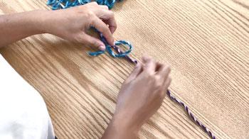 反対側は、下の糸を反時計回りに上の糸に重ね、下をくぐらせて下側の糸に結びつけます。