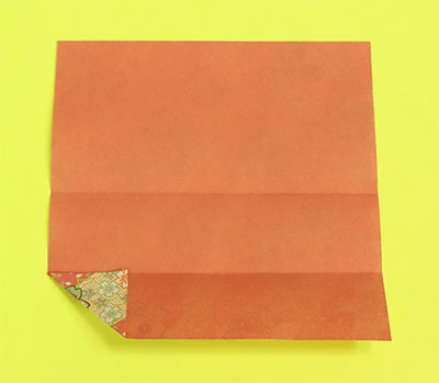 開いて折り筋に合わせて左の角を三角に折ります。