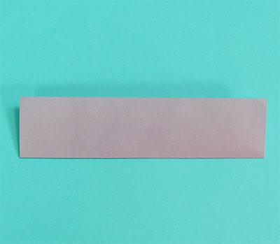 切った半分の折り紙を、さらに半分にしっかり折って、開きます。