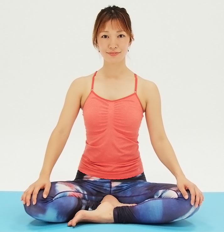 あぐらの姿勢で座り、骨盤をしっかり立てて背骨をまっすぐ上に引き上げます。あごは軽く引いておきましょう。