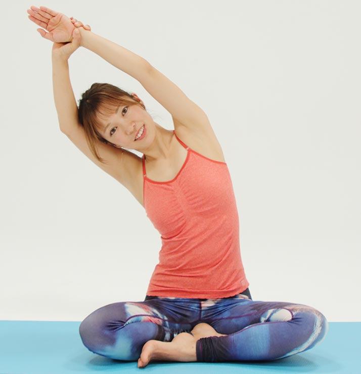 吐きながら、肩から手を遠くに伸ばすように体を横に倒して体側を伸ばします。吸いながら戻します
