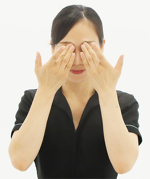 両手中指を小鼻のきわに当て、小鼻と目頭の間を上下にスライド