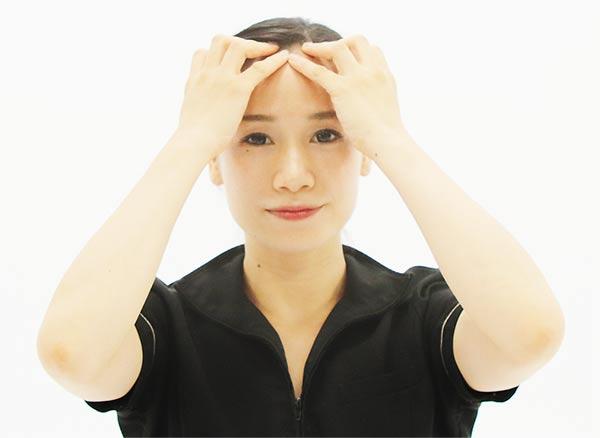 五本指を開いて頭の真ん中生え際におき、生え際から後頭部に向かってスライド