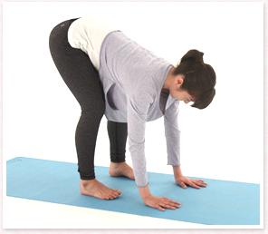 足は腰幅に開いて立ち両ひざを軽く緩め両手を床へ。前屈のポーズ
