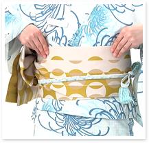 帯を下ろして形を整え、帯が崩れないように右袖を上げ、帯を帯板と一緒に右に回します。このとき左に回すと衿が崩れてしまうので必ず右に回しましょう。