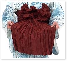 短い方の帯は、広げて、帯の端を結び目の下からくぐらせます。