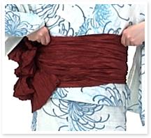 帯が崩れないように右袖を上げ、帯板と一緒に帯を右に回します。このとき左に回すと衿が崩れてしまうので必ず右に回しましょう。