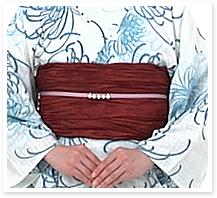 結び目を後ろに回して帯の下に隠します。帯留めを体の中心に揃えて完成です。