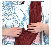 短い方の帯を、輪が外側になるようして左肩にあずけ、クリップの位置を帯の真中に合わせ、一旦、クリップで帯を帯板に留めておきます。