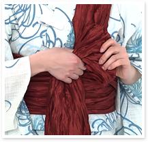 長い方の帯を、一旦、肩にあずけ、垂れている短い方の帯で10㎝程度の小さめの羽根を作ります。