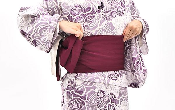 帯が崩れないように右袖を上げ、帯板と一緒に帯を右に回し、帯板が体の正面まで来たら一旦止めます。
