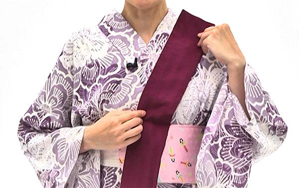 帯の手先を半分に折り、輪を外にして左肩に掛けます。 帯板にかかるくらいの長さにします。