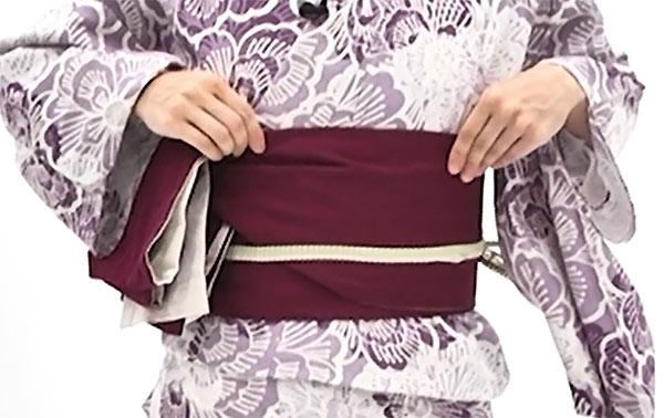 帯が崩れないように右袖を上げ、帯板と一緒に帯を右に回し、帯板が体の正面まで来たら一旦止めます